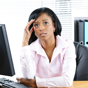 Worried young woman at computer