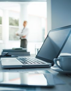 Businessman standing with arms crossed outside his office, desktop with laptop on foreground, selective focus